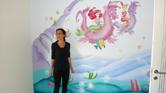 ציור קיר ובצידו ציירת קירות אנה קוגן