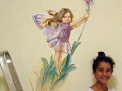 ציור קיר של פיה עומדת על פרח בחדר של נערה