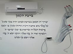 ציור הקיר של ברכת העסק וכף היד ומחרוזת פנינים בסלון ציפורניים בחדרה