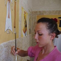 אנה קוגן מציירת ציור קיר בסגנון מצריים העתיקה בסלון בבית פרטי בתרום